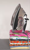 Pile of colorful clothes and electric iron — Stock Photo