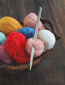 Colorful yarn and knitting needle on a wooden table — Stock Photo