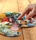 Hand with palette-knife and palette — Stock Photo