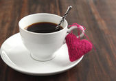 Cup of coffee with knitted heart — Stock Photo
