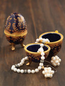 Egg shaped casket with a pearl necklace and earrings — Stock Photo