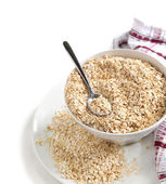 Oat flakes in bowl on white background — Stock Photo