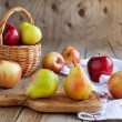 Fresh ripe pears and apples on wooden table — Stock Photo #24220565