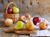 Fresh ripe pears and apples on wooden table — Stock Photo