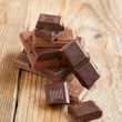 Broken chocolate bar on wooden background. Selective focus — Stock Photo
