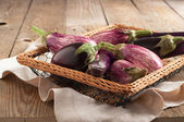 Various Eggplants on wooden table — Stock Photo