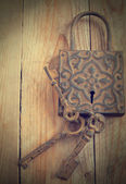 Old decoration lock and keys on wooden background — Stock Photo