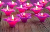 Gruppo di candele accese su sfondo in legno. — Foto Stock
