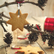Photo: Gingerbread cookie hanging on branch with pine cones . Selective