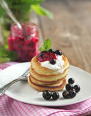 Pancakes with sour cream and black currant jam — Stock Photo