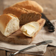 Whole grain bread and white bread on wooden chopping board. — Stock Photo #29840665