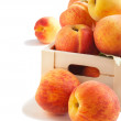 Fresh peaches in wooden box isolated on white background — Stock Photo
