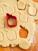 Apple shaped cookie cutter on raw cookie dough — Stock Photo