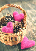 Pine cones and handmade crochet hearts in basket — Stock Photo