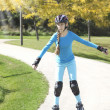 Stock Photo: Teenage girl rollerskating in park