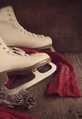 Skates for figure skating on a wooden background, toned — Stock Photo