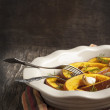 Stock Photo: Baked pumpkin slices with garlic. Toned image