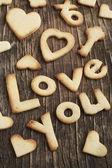 Metin şekerli kurabiye ahşap zemin üzerine gelen aşk — Stok fotoğraf