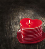 Red burning heart shaped candles on wooden background. — Stok fotoğraf