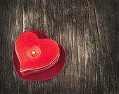 Red burning heart shaped candles on wooden background. — Stock Photo