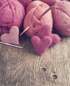 Crochet pink hearts and yarn on wooden background. — Stock Photo