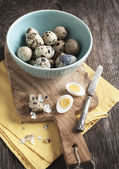 Fresh hard boiled quail eggs with shell beside on cooking board — Stockfoto