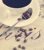 Cup of coffee and coffee beans. Selective focus on coffee beans — Stockfoto