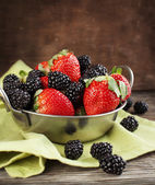 Fresh strawberries and blackberries in bowl on wooden background — Foto Stock