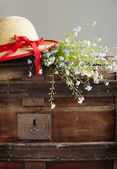 Blue summer flowers and straw hat on old vintage chest  — Foto Stock