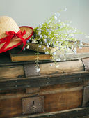Summer blue flowers and straw hat on old vintage chest — Stock fotografie