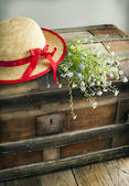 Blue summer flowers and straw hat on old vintage chest  — Foto de Stock