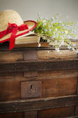 Summer blue flowers and straw hat on old vintage chest — Stockfoto
