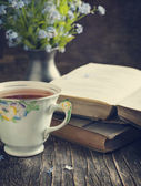 Cup of tea, vintage books and  summer blue flowers on the table. — Stockfoto