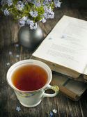 Cup of tea, vintage books and  summer blue flowers on the table. — Stock Photo