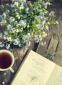 Bouquet of summer blue flowers, cup of tea and vintage books — Stock Photo