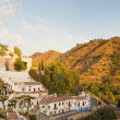 Panoramic photo overviewing the district of Sacromonte at sunset. White houses. Mountains with trees. Blue cloudy sky. Granada. Andalusia. Spain. — Stock Photo