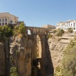 Panoramic photo of the famous bridge over the canyon of the Guadalevin river in Ronda. Puente Nuevo. Malaga. Andalusia. Spain. — Stock Photo