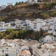 Stock Photo: Panoramic photo overviewing pueblo blanco Setenil de las Bodegas. Old white village. Blue sky. Cadiz. Andalusia. Spain.