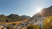 Panoramic photo overviewing pueblo blanco Villaluenga del Rosario at sunset. Old white mountain village. Sierra de Grazalema. Blue sky. Sunshine. Cadiz. Andalusia. Spain. — Stock Photo