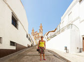 Panoramic photo of female tourist in the street of the pueblos blancos Olvera. Neoclassical cathedral. Iglesia de Nuestra Senora. Old white village. Blue sky. Cadiz. Andalusia. Spain. — Stock Photo