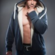 Muscled fitness man. Cool looking. Tough guy. Brown eyes. Bald. Wearing blue hoody shirt. Tanned skin. Studio shot isolated on grey background. — Stock Photo #13166667
