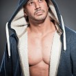 Muscled fitness man. Cool looking. Tough guy. Brown eyes. Bald. Wearing blue hoody shirt. Tanned skin. Studio shot isolated on grey background. — Stock Photo #13166677