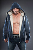 Muscled fitness man. Cool looking. Tough guy. Brown eyes. Bald. Wearing blue hoody shirt. Tanned skin. Studio shot isolated on grey background. — Stock Photo