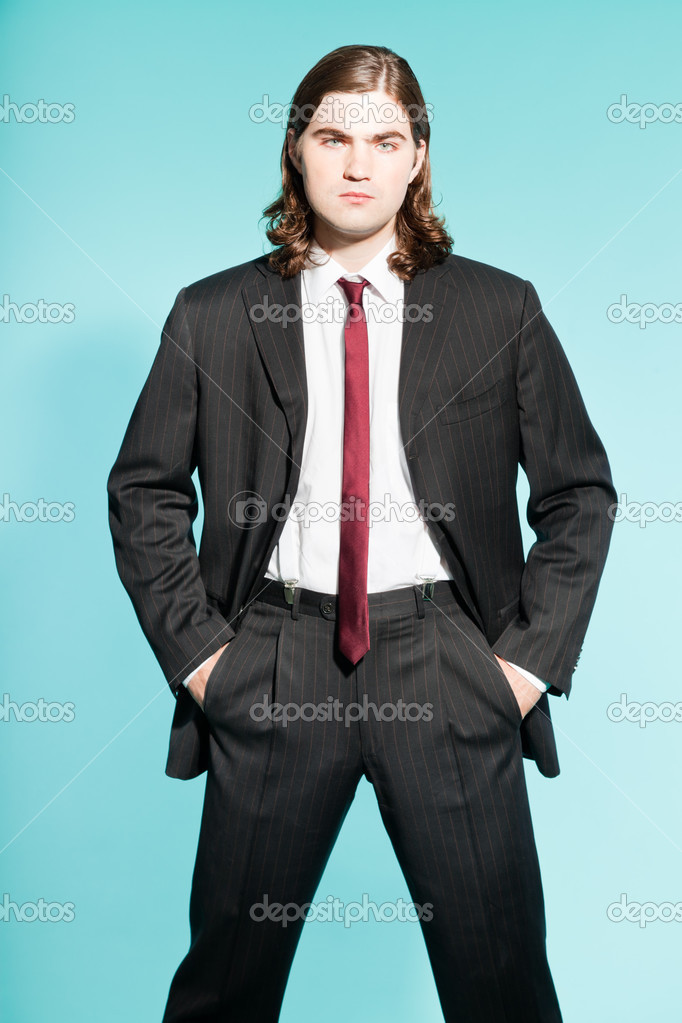 Cool business man with long brown hair confident looking. Wearing black striped suit and dark red tie. Standing out guy.  Stock Photo #13455977