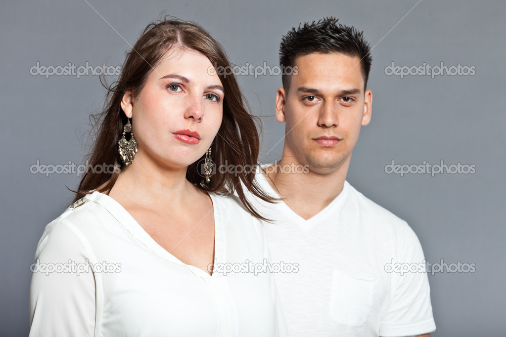 Diverse young happy couple together. Dressed in white. Laughing and having fun. Studio shot. Isolated on grey background.  — Stock Photo #13474392