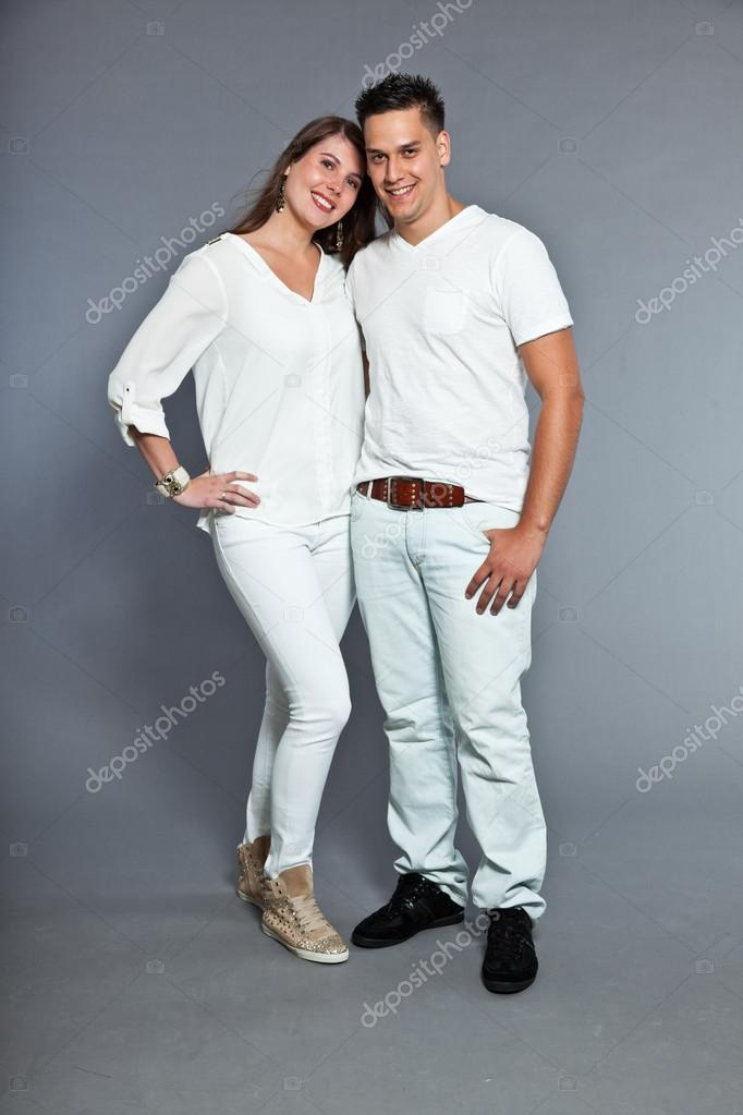 Diverse young happy couple together. Dressed in white. Laughing and having fun. Studio shot. Isolated on grey background.  — Stock Photo #13474396