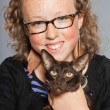 Happy teenage girl with glasses and blond curly hair hugging dark brown oriental shorthait cat. - Stock Photo