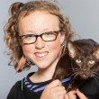 Stock Photo: Happy teenage girl with glasses and blond curly hair hugging dark brown oriental shorthait cat.