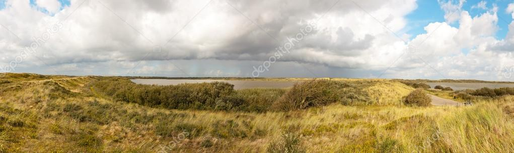 Panoramic shot of dutch dune landscape with lakes and stormy blue cloudy sky. The Hors lakes. Texel. Wadden island. The Netherlands. — Stock Photo #13520809