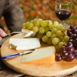 Table with plate of cheese, grapes and red wine. — Stock Photo